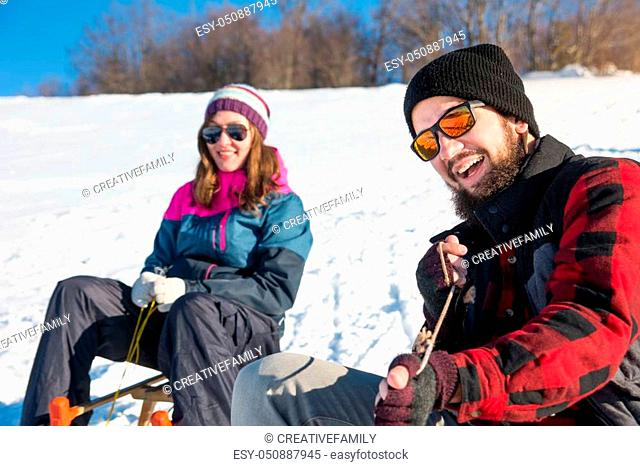 Happy young couple sledding down the hill