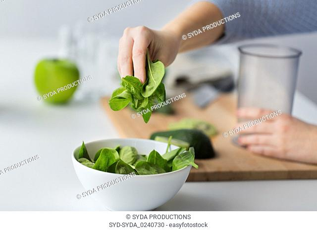 close up of woman hand adding spinach to bowl