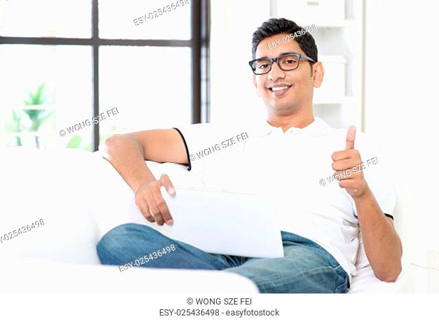 Portrait of Indian guy giving thumb up while using digital tablet computer at home. Asian man relaxed and sitting on sofa indoor. Handsome male model