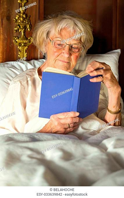 Elderly woman in her nightgown wearing glasses sitting propped up against the pillows reading a hardcover book in bed