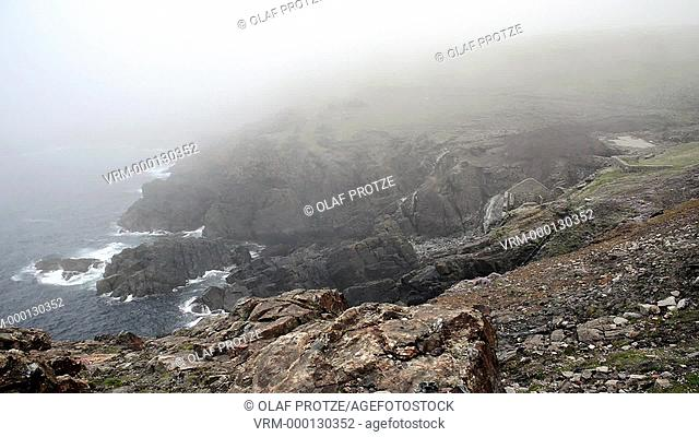 Misty view of the Geevor Tin Mine and coastline before, Cornwall, England, UK