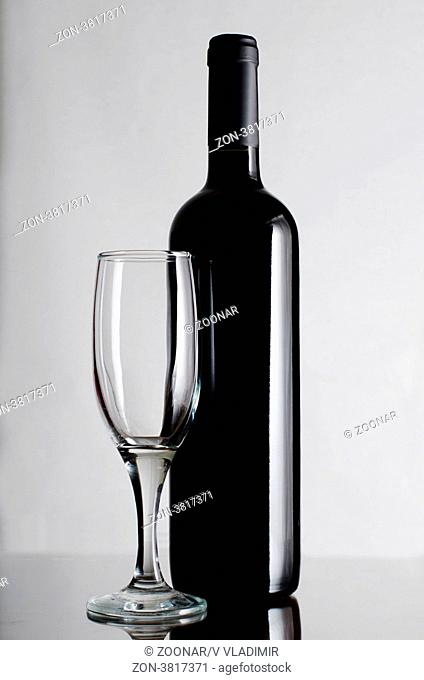 Red wine bottle on a grey background