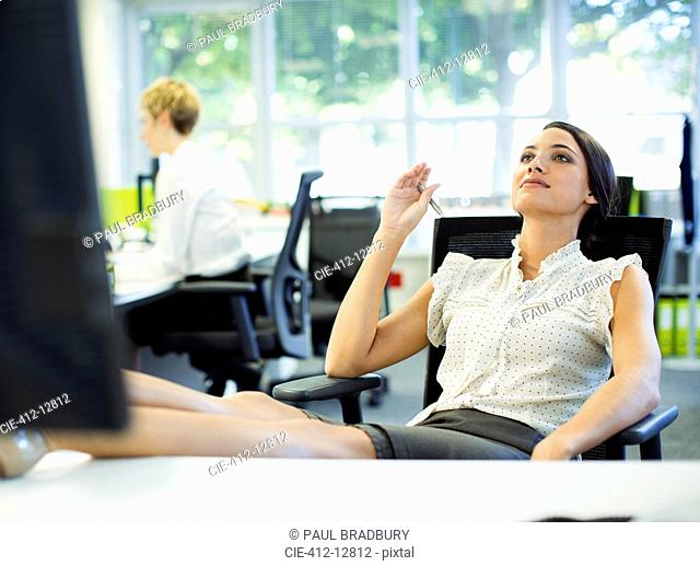 Businesswoman relaxing with feet up on desk in office