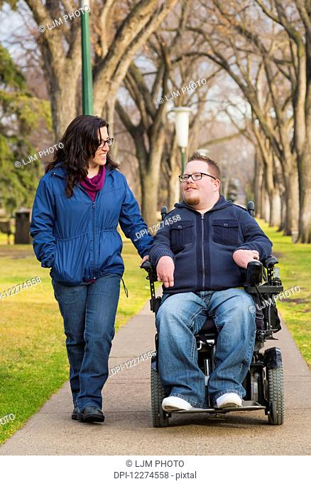 Disabled husband talking with his wife while walking in a park in autumn; Edmonton, Alberta, Canada