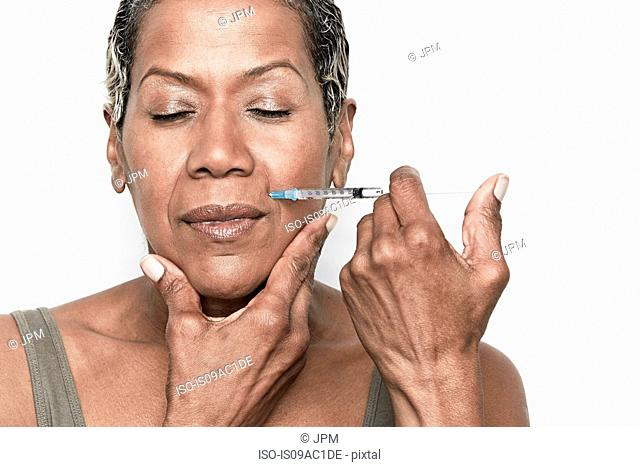 Senior woman injecting herself with botox