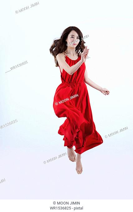 a woman in a red dress floating in the air