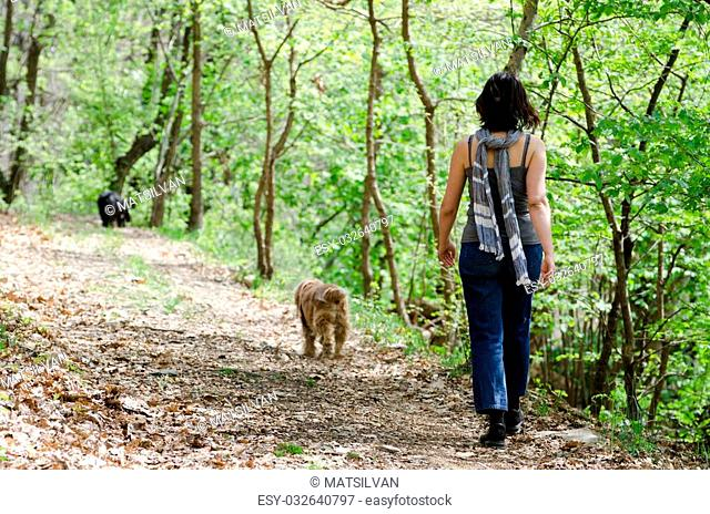 Woman walking in the forest with her two dogs