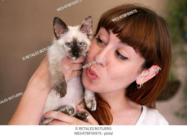 Portrait of young woman with kitten