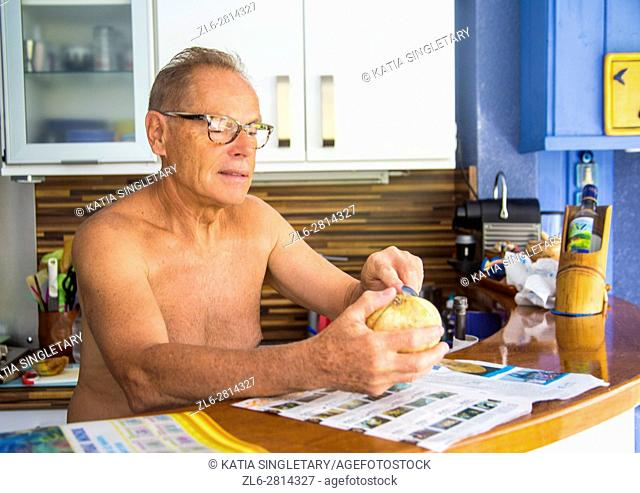 Older senior caucasian retired man without a shirt cooking cutting cantaloupe in the kitchen for lunch