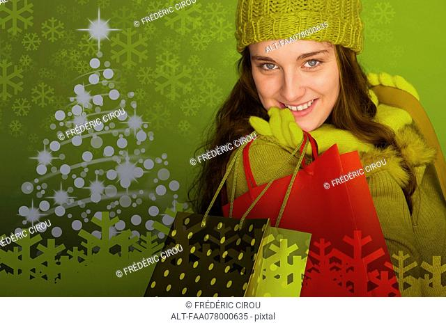 Young woman carrying Christmas shopping bags, portrait