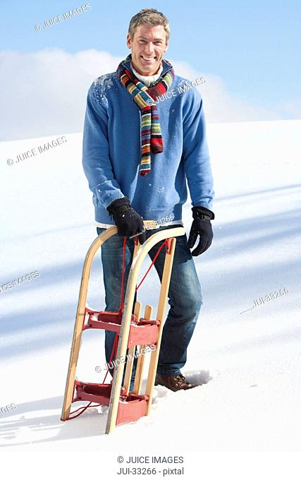 Portrait of smiling man with sled in snow
