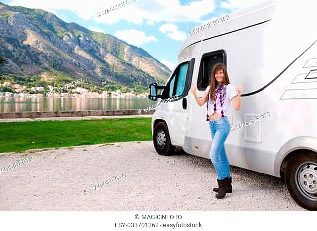 Happy young woman near camper
