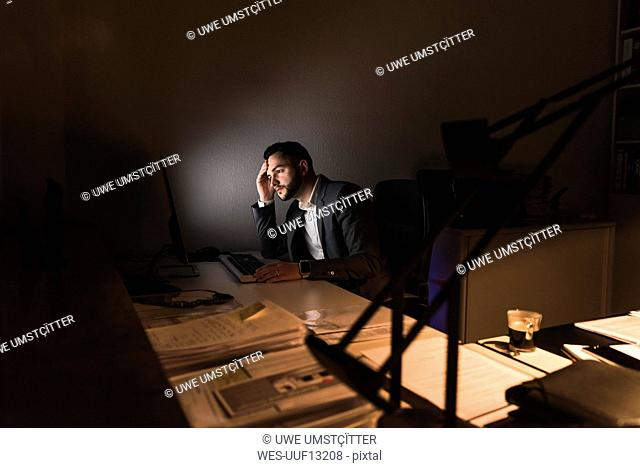 Pensive young businessman sitting at desk in office at night