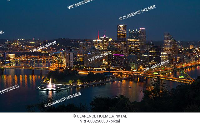 (Time-lapse) Night falls on the downtown area of Pittsburgh, Pennsylvania including the skyline, bridges, and Point State Park at the confluence of the...