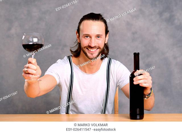 young man in front of gray background drinking red wine