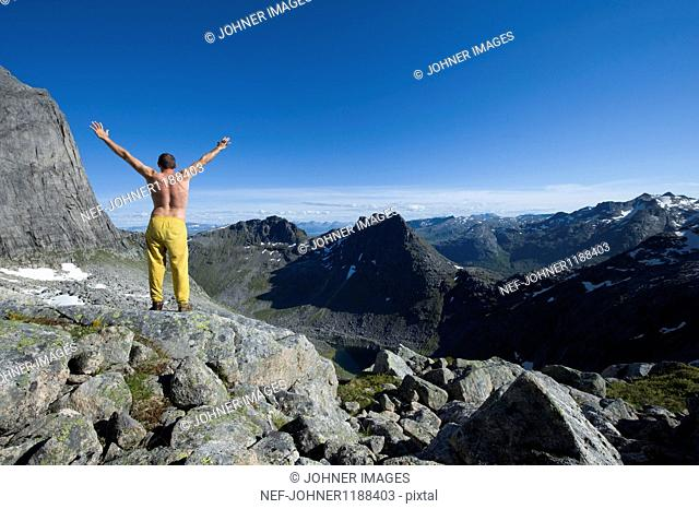 Shirtless man standing on mountain peak with arms raised