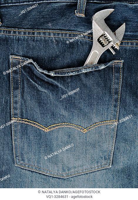 metal adjustable wrench in blue jeans back pocket, full frame