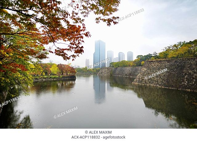 Osaka downtown Chuo-ku financial distric high-rise towers, Crystal tower and other buildings view from Osaka Castle Park moat in colorful autumn foggy scenery