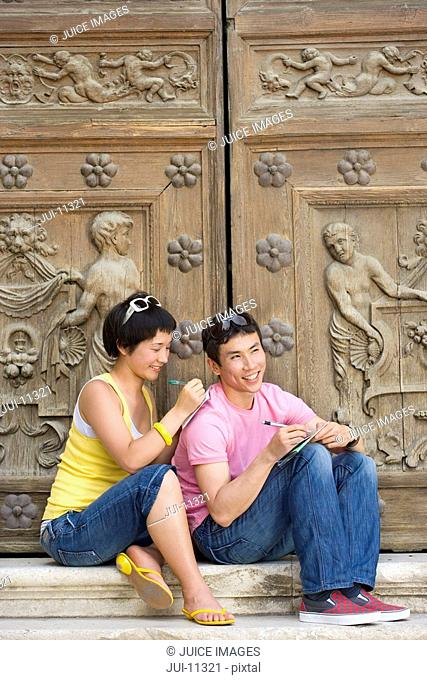 Couple on steps by wooden doors writing, smiling
