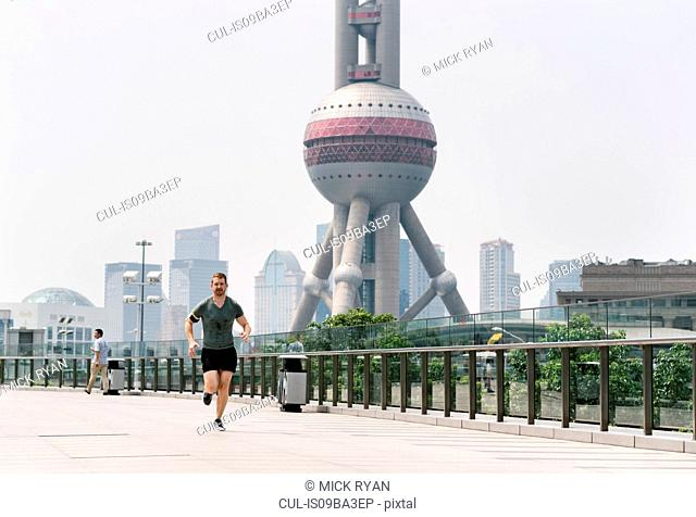 Young male runner running in Shanghai financial centre, Shanghai, China