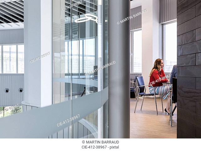 Businesswoman listening in modern conference room meeting