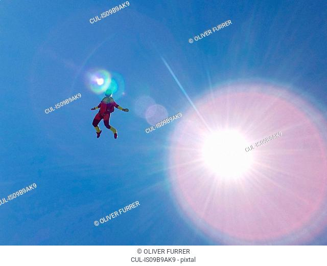 Female skydiver free falling upright against sunlit blue sky