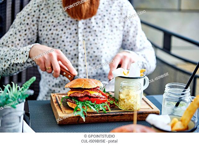 Bearded man eating burger, cropped