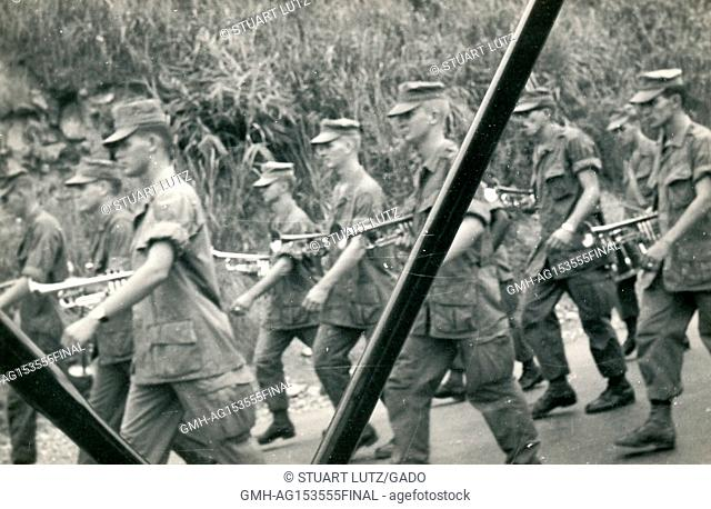 A United States Marine Corps band marches while holding instruments during the Vietnam War, 1968. ()