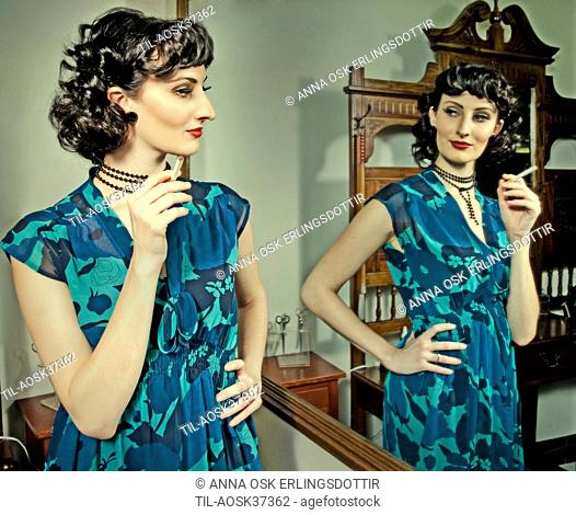 Lone female figure holding cigarette looking into mirror