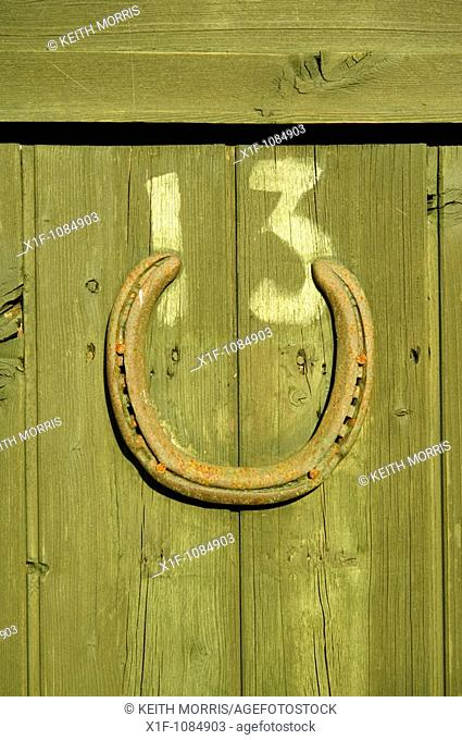 Unlucky number 13 with lucky horseshoe on wooden door on an allotment garden shed, Aberystwyth Wales UK