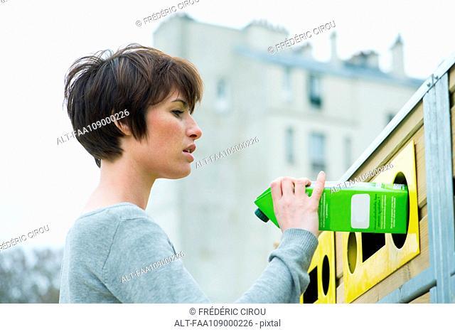 Woman placing carton in recycling bin