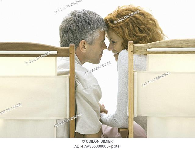 Mature couple sitting in beach chairs, touching foreheads