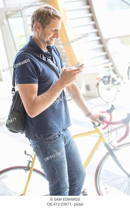 Man using cell phone and holding bicycle