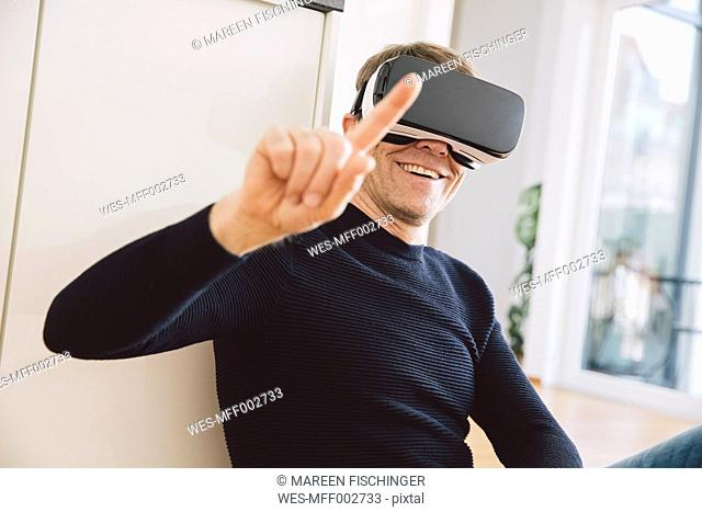 Smiling man wearing virtual reality glasses pointing his finger