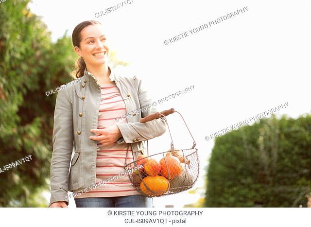 Woman carrying basket of organic fruit and veg