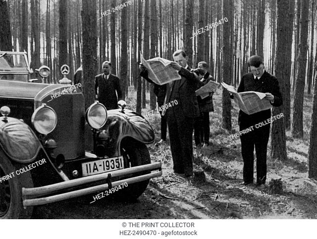 A break in the woods, 1936. Nazi leader Adolf Hitler (1889-1945) and colleagues reading the papers while they take a break during a car journey
