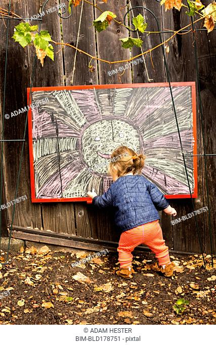 Caucasian baby girl drawing outdoors