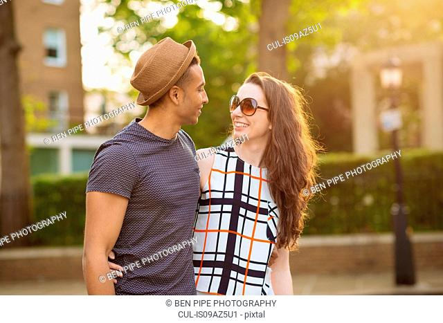 Young couple walking in street face to face smiling