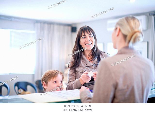 Mother and son making appointment at hospital reception