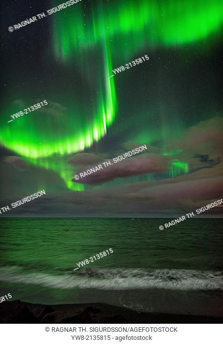 Aurora Borealis or Northern lights over waves breakiing on the beach in Seltjarnarnes, Reykjavik, Iceland