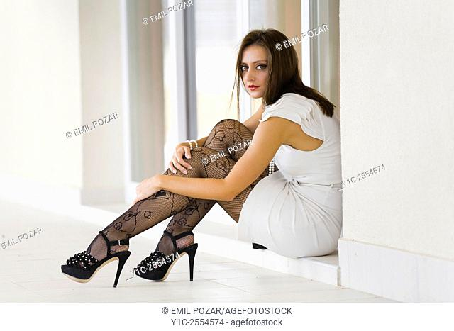 Stock Photo - Young woman fashionable in White dress and fishnets