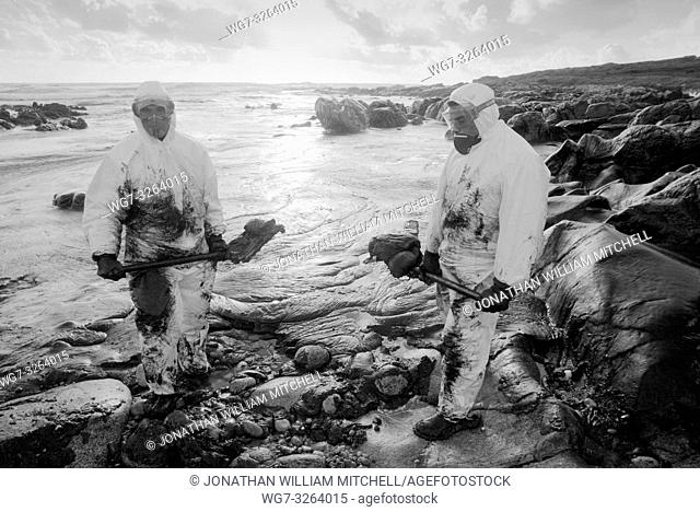 SPAIN Muxia -- 30/11/2002 -- Volunteers cleans oil from rocks on the beach at Muxia. Thousands of tonnes of heavy fuel oil which has leaked from the sunken...