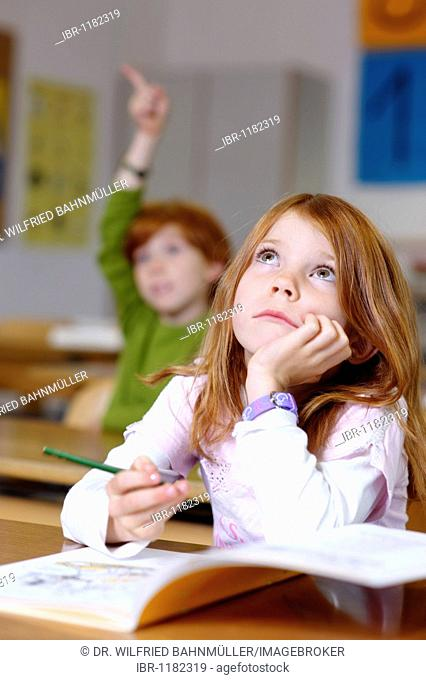 Children in a classroom in primary school, girl daydreaming or looking unsure, thoughtful, sad or frustrated, equal oppurtunity in the education system