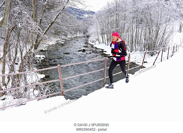 A woman jogging on a bridge over a snowy winter river