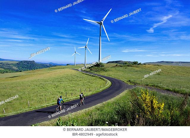 Cyclists on walk in the Cezallier wind farm, Puy de Dome department, Auvergne Rhone Alpes, France