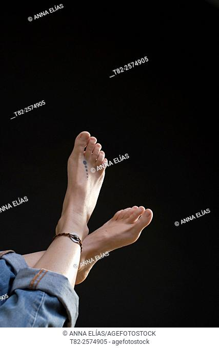 feet of young woman on black background