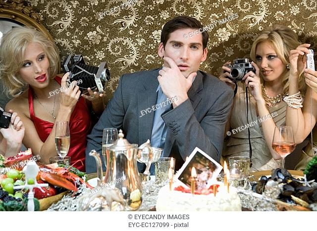 Young man posing for female photographers at dinner party