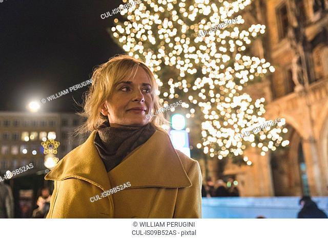 Woman waiting by illuminated christmas tree at night, Munich, Germany