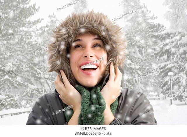 Mixed race woman in fur hood watching snow fall