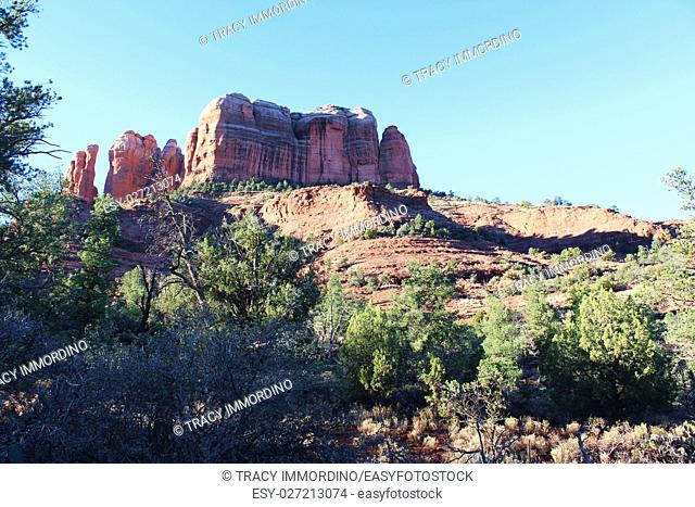 Hiking the Cathedral Rock Trail with a multi hued butte and red rock pinnacles in the background and red rock hills and trees in the foreground